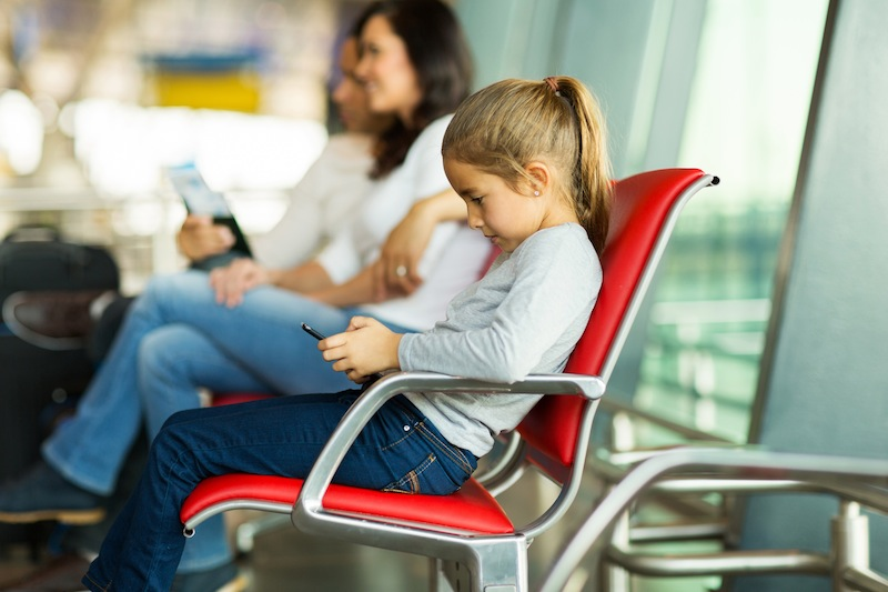 young girl playing with tablet pc at airport