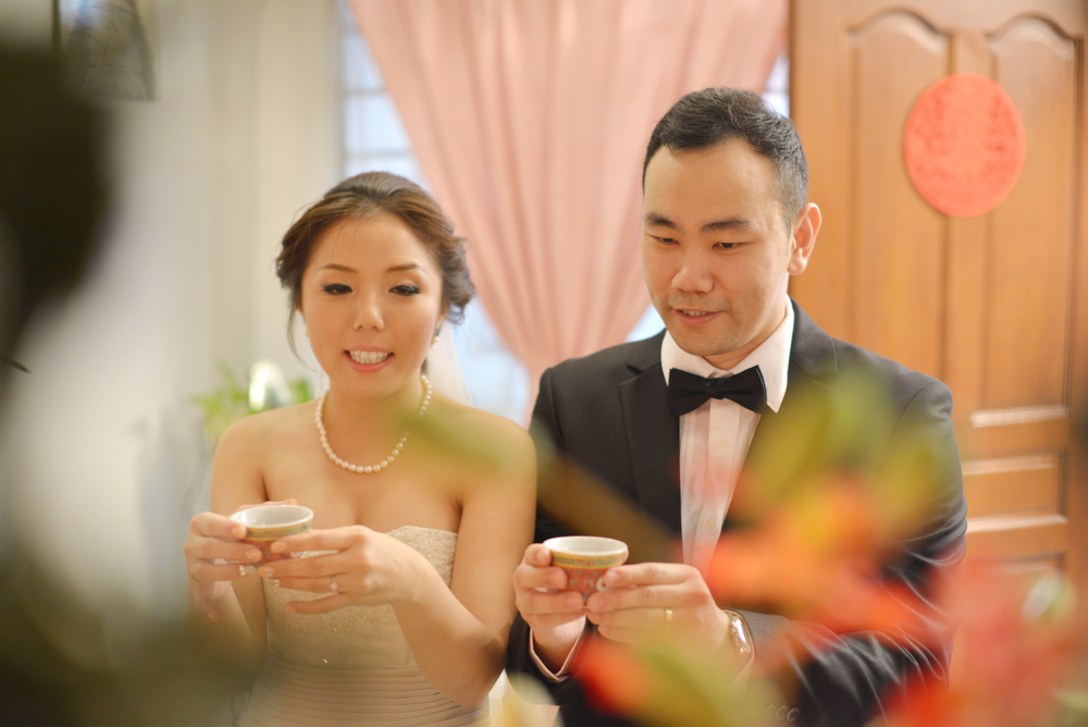 Traditional Chinese wedding, bride and groom serving tea in ceremony.