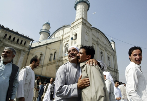 Afghans celebrate the Eid al Adha each other after offering Eid al Adha's prayers outside Shah-e-Dushamshera mosque in Kabul, Afghanistan, Thursday, August, 8, 2013. Eid al-Adha is a religious festival celebrated by Muslims worldwide at the end of the holy fasting month of Ramadan. (AP Photo/Ahmad Nazar)