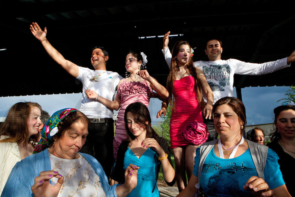 Parents and relatives celebrates a wedding dancing. Each spring in Mogila, Bulgaria, is celebrated the Gypsy Bride Market. In this festival the virginity is for sale. The honor can be bought. Every girl has a price to be agreed between the parents of the girl and the candidate. The price can range between 1.500 and 10.000?, in a country where the minimum salary is just over 100?. The market joins the Kalajdzii families, known as the thracians tinkerers, whose tradition is still alive. Many girls dress as real princesses, others prefer to dress in a modern way. They dance during hours the ring dance while grandparents and parents watch the way the young interrelate. Many girls dream to be married by the rite imposed by the tradition. Nowadays there are some girls that don?t agree with the tradition and would prefer not to marry, although they assist to these market all the times. Divorces and elopements, so far taboo, are becoming everytime more frequent. Beyond the topic, ethnologists, define it as the Kalajdzii?s disco, where the family honor is involved in a commercial transaction. This ritual has being celebrated for years, so anthropologists think is not going to change too much in future.
